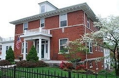 Large two-story brick house with columned porch and black wrought-iron fence